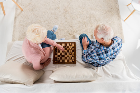 top view of senior couple playing chess at home on couch