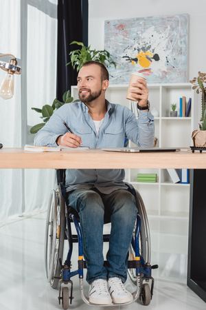 thoughtful disabled man on wheelchair sitting at worktable with disposable cup of coffee