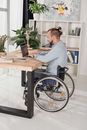 disabled man on wheelchair using laptop at office 스톡 콘텐츠