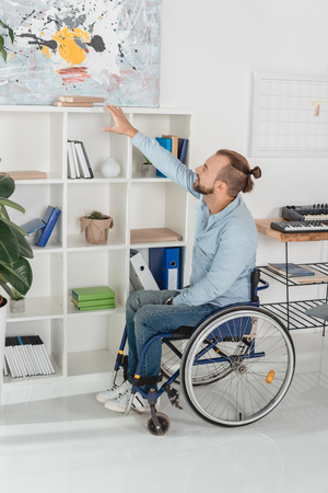 young disabled man on wheelchair trying to reach for book on bookshelves
