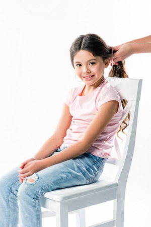 Cropped image of mother tying daughters hair in ponytail isolated on white Stockfoto - 104665037
