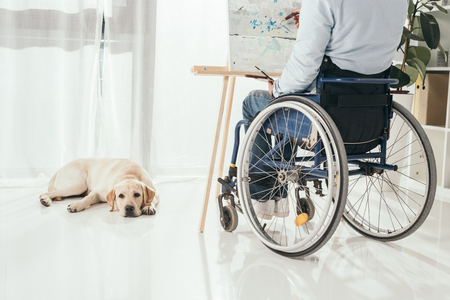 cropped shot of disabled man on wheelchair painting while his dog laying on floor