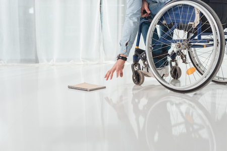 cropped shot of disabled man on wheelchair trying to reach for book laying on floor Banco de Imagens