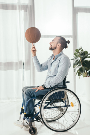 disabled man on wheelchair spinning basketball ball on finger Archivio Fotografico - 104665231
