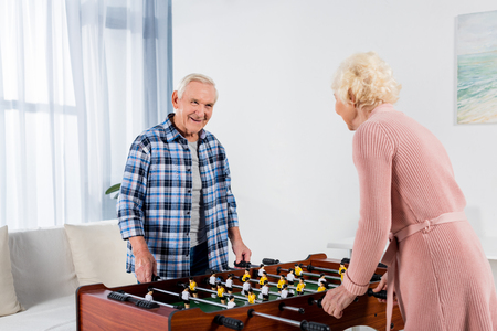 happy senior couple playing table football