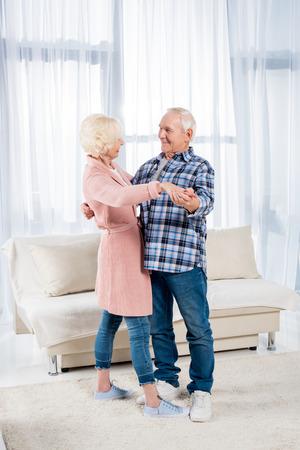 side view of smiling senior couple dancing together at home Standard-Bild - 104665319