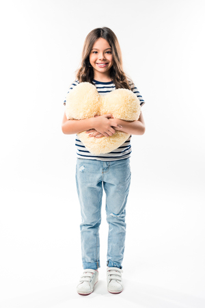 Smiling child standing and holding heart shaped pillow isolated on white 写真素材