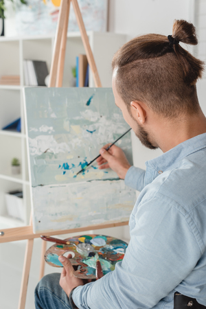 man painting abstraction on canvas with oil paint Archivio Fotografico - 104665329