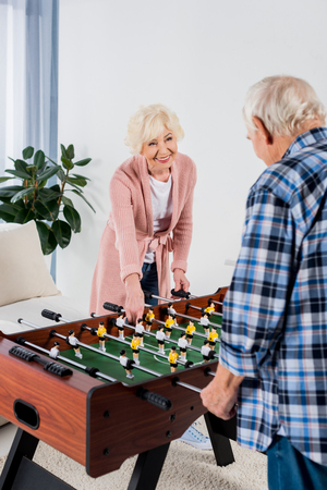 beautiful senior couple playing table football at home