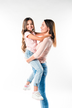 Mother holding smiling daughter on hands isolated on white