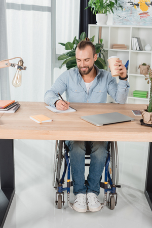 disabled man on wheelchair sitting at worktable with disposable cup of coffee and writing Imagens