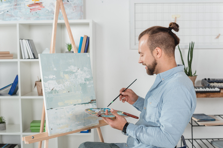 smiling young man painting on canvas with oil paint on palette Archivio Fotografico - 104665917