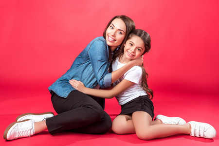 Daughter and mother sitting and hugging on red Foto de archivo - 104665919