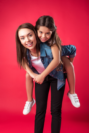 Happy mother giving piggyback to her daughter isolated on red