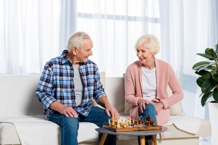 senior couple playing chess at home while sitting on couch Stok Fotoğraf