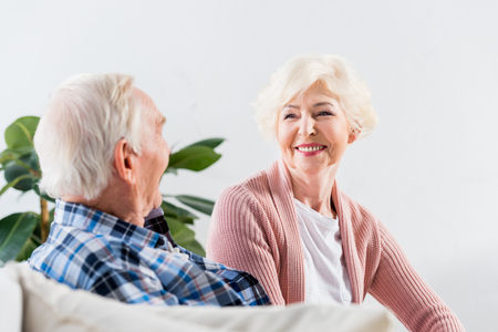 beautiful senior couple sitting on couch at home and talking