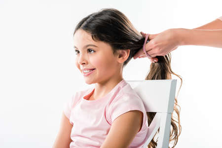 Cropped image of mother tying daughters hair in ponytail with elastic band isolated on white