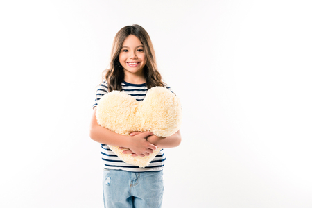 Smiling female kid holding heart shaped pillow isolated on white Stock Photo