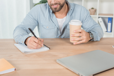 cropped shot of man writing in notebook and drinking coffee at workplace