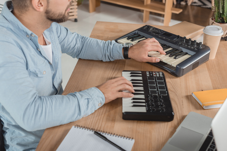 cropped shot of focused sound producer working with mpc pads