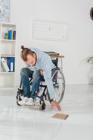 disabled man on wheelchair trying to reach for book laying on floor