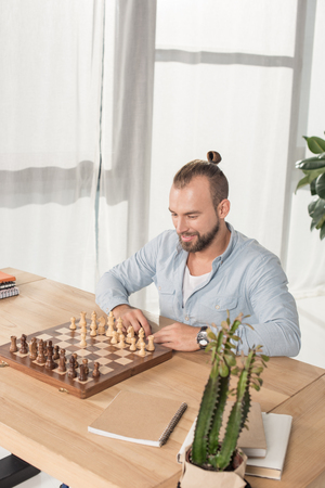young smiling man playing chess with himself