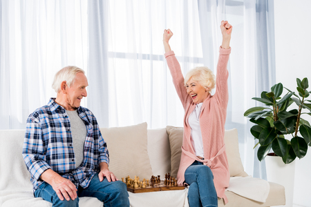 happy senior couple playing chess at home on couch