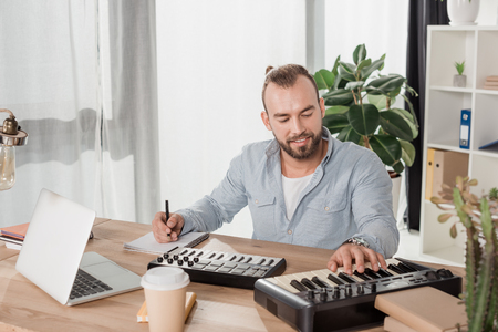 happy concentrated sound producer working with mpc pads at office Stock Photo