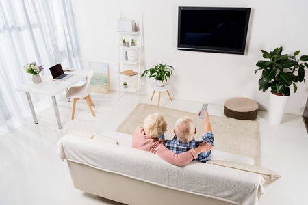 senior couple watching television on cozy couch at home