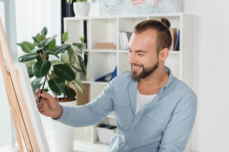 handsome smiling man painting on canvas with oil paint Archivio Fotografico - 104726628
