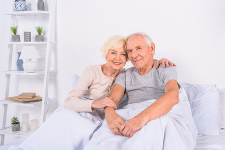 portrait of smiling senior couple resting in bed and looking at camera at home Standard-Bild - 104726660