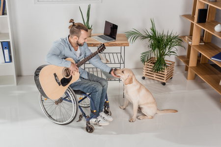 disabled man on wheelchair with guitar petting adorable dog