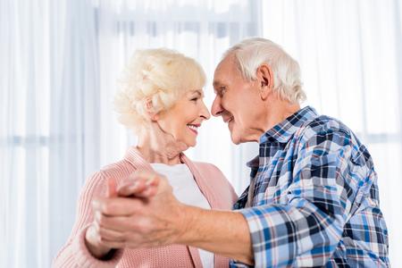 side view of smiling senior couple dancing together at home Standard-Bild - 104726675