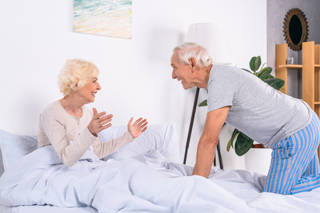 side view of happy senior wife and husband resting in bed at home Standard-Bild - 104727134