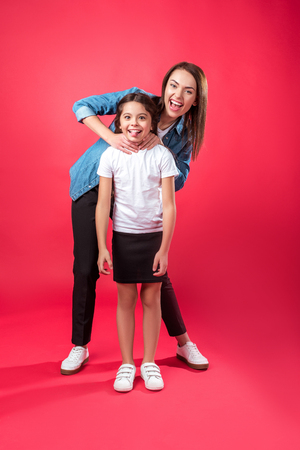 Mother and daughter having fun and imitating choking on red Stock Photo