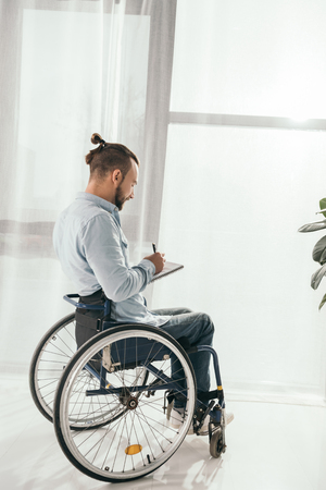 disabled man on wheelchair writing in notebook in front of window