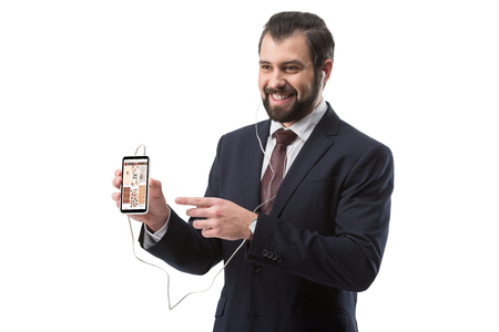 Cheerful bearded businessman listening music with earphones and pointing at smartphone with pinterest website, isolated on white