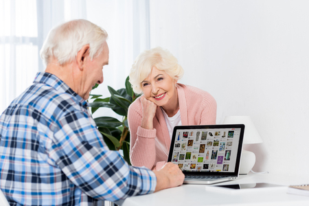 portrait of happy senior woman looking at husband using laptop with pinterest logo at home