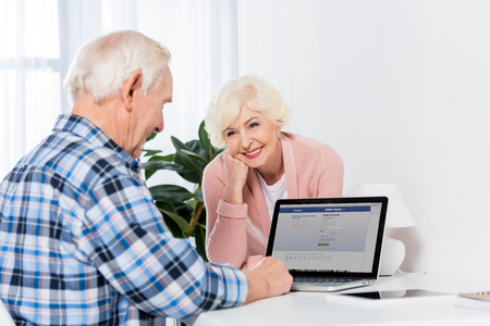 portrait of senior woman looking at husband working on laptop with facebook logo at home
