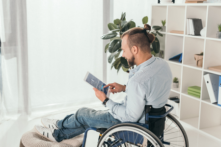 handsome disabled man on wheelchair using digital tablet with tumblr website Editorial