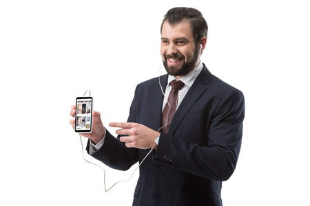 cheerful bearded businessman listening music with earphones and pointing at smartphone with pinterest website, isolated on white Editorial