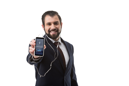 Bearded businessman with earphones showing smartphone with tumblr website, isolated on white