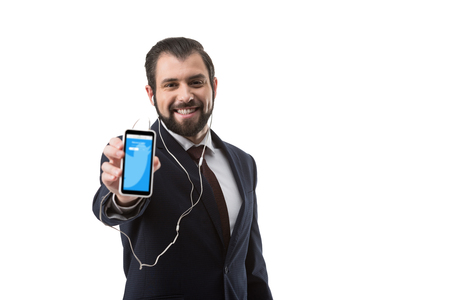 Bearded businessman with earphones showing smartphone with twitter website, isolated on white Stock Photo - 105373459