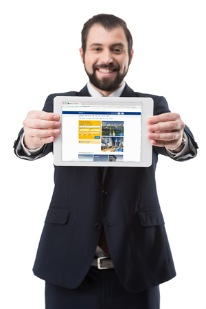 Smiling businessman showing digital tablet with booking website, isolated on white Editorial