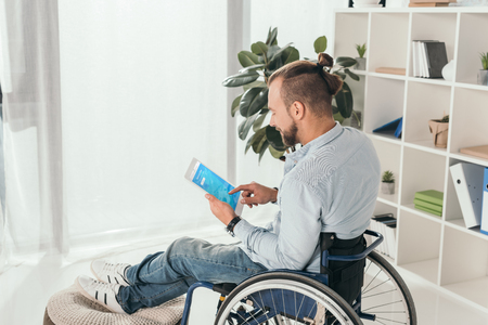 handsome disabled man on wheelchair using digital tablet with twitter web page