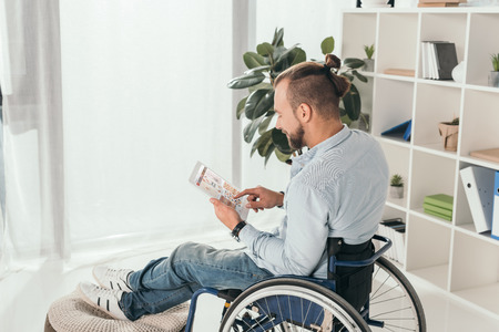 handsome disabled man on wheelchair using digital tablet with pinterest website Editorial