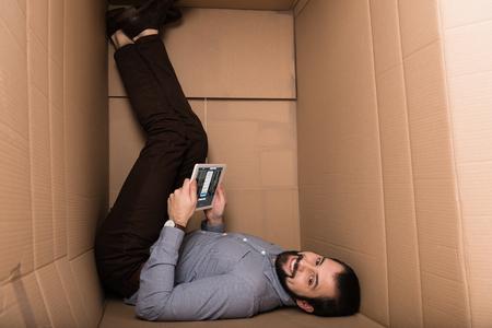 handsome man using digital tablet with linkedin website in cardboard box Editorial