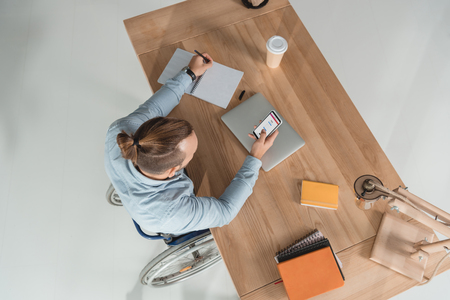 high angle view of disabled man on wheelchair using smartphone at workplace in office with instagram app Editorial
