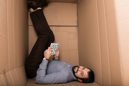 smiling introvert using digital tablet with pinterest website in cardboard box