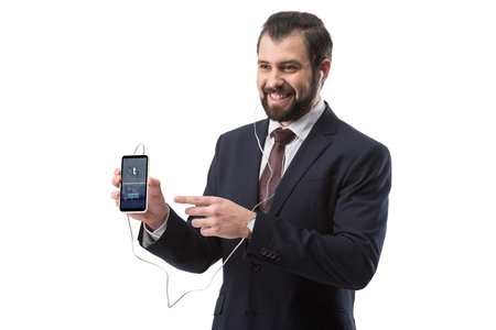 Cheerful bearded businessman listening music with earphones and pointing at smartphone with tumblr website, isolated on white